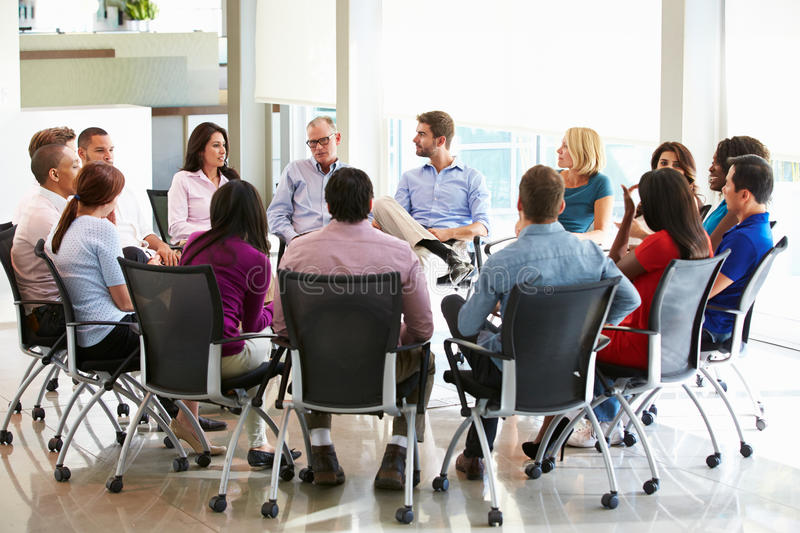 Multi-Cultural Office Staff Sitting Having Meeting Together. In Boardroom stock photography