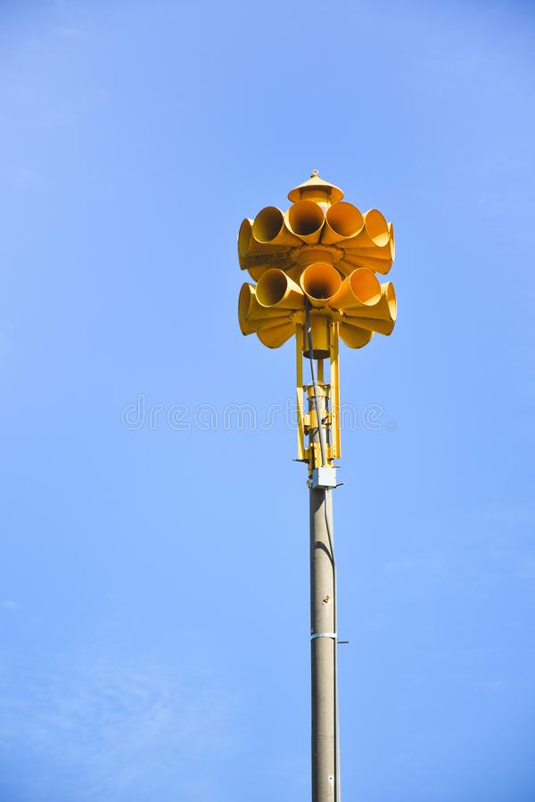 Multi directional yellow round amplified emergency siren. Photograph of several multi directional round yellow amplified emergency sirens on top of a pole in a royalty free stock image
