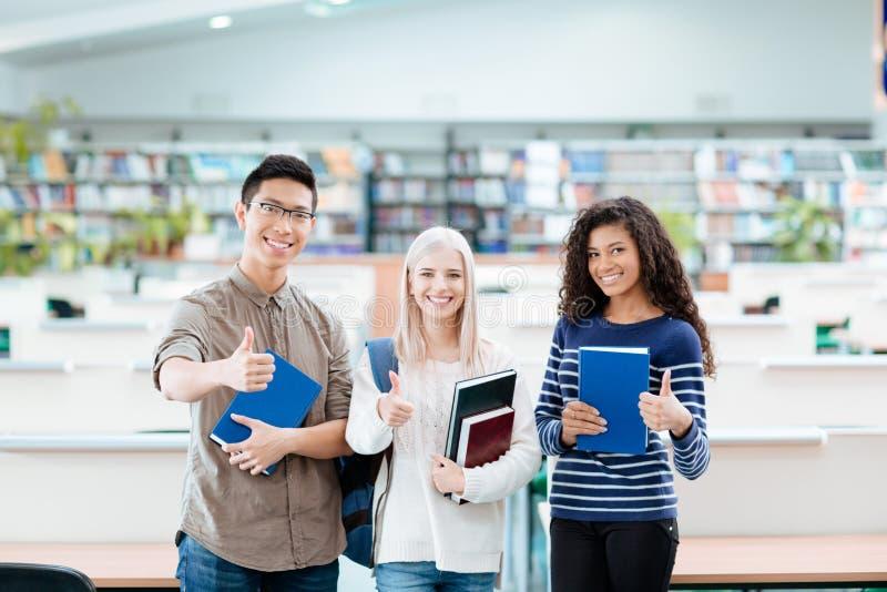Multi estudantes etchnic felizes que estão na biblioteca da universidade fotografia de stock