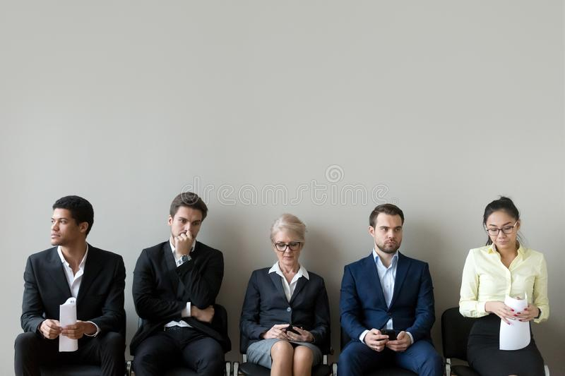 Multi-ethnic applicants sitting in row queue line preparing for interview royalty free stock images