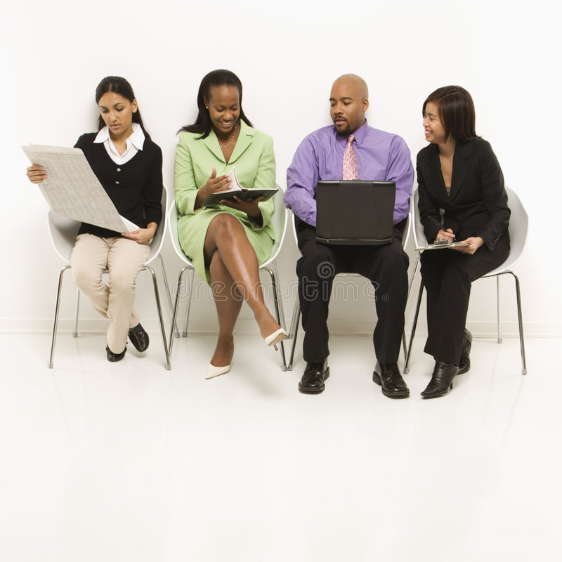 Multi-ethnic business group. Of men and women sitting looking at laptop and papers