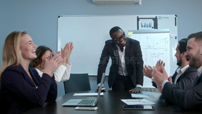 Multi ethnic business group greets afro-american boss with clapping and smiling. Professional shot in 4K resolution. 085. You can use it e.g. in your royalty free stock images