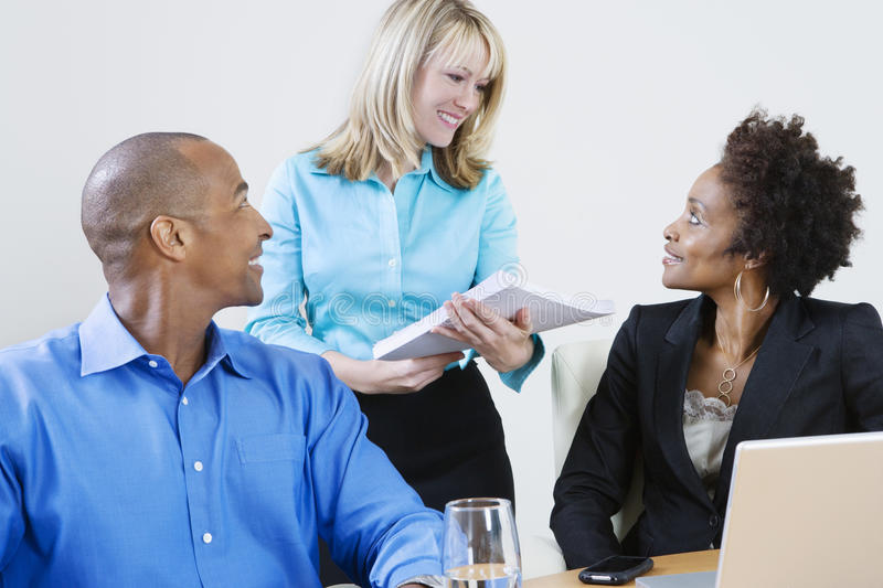 Multi Ethnic Business People Communicating. Happy multi ethnic business people communicating with each other royalty free stock photography