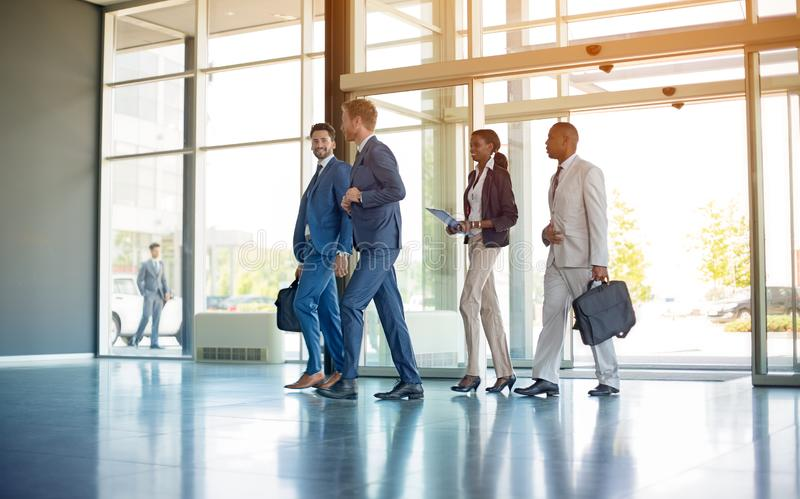 Multi ethnic business people on the way in building stock photos