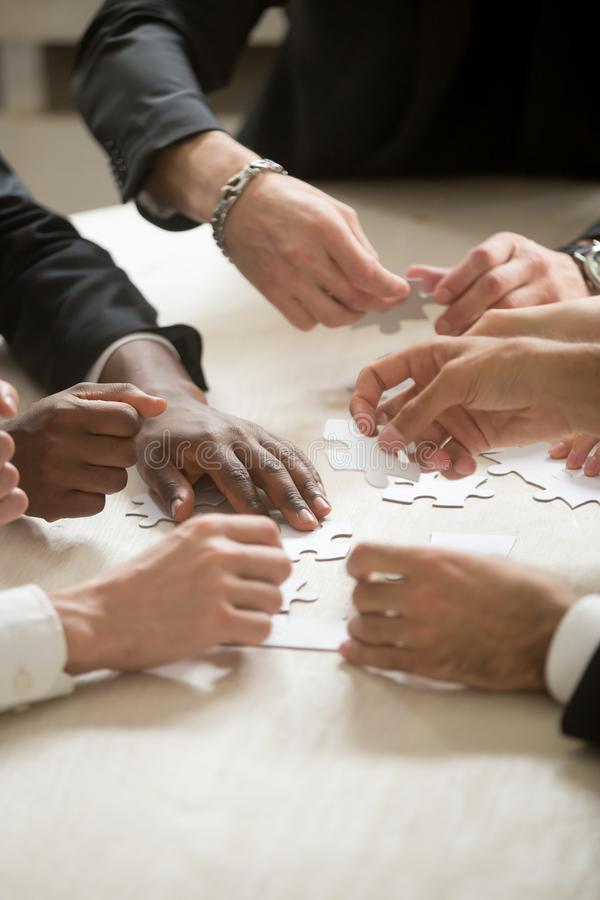 Multi-ethnic business team assembling jigsaw puzzle together, ve. Multi-ethnic group of people assembling jigsaw puzzle together, hands joining pieces at desk stock photo