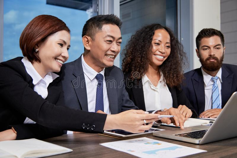 Happy business people reading good news on laptop screen stock photography