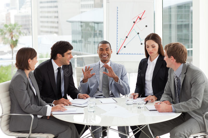 Multi-ethnic business team working together in a m. Eeting stock images