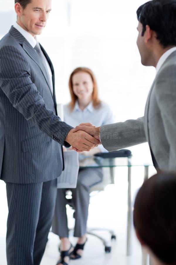 Multi-ethnic businessmen shaking hands stock image