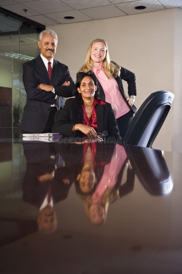 Multi-ethnic businesspeople in boardroom stock image