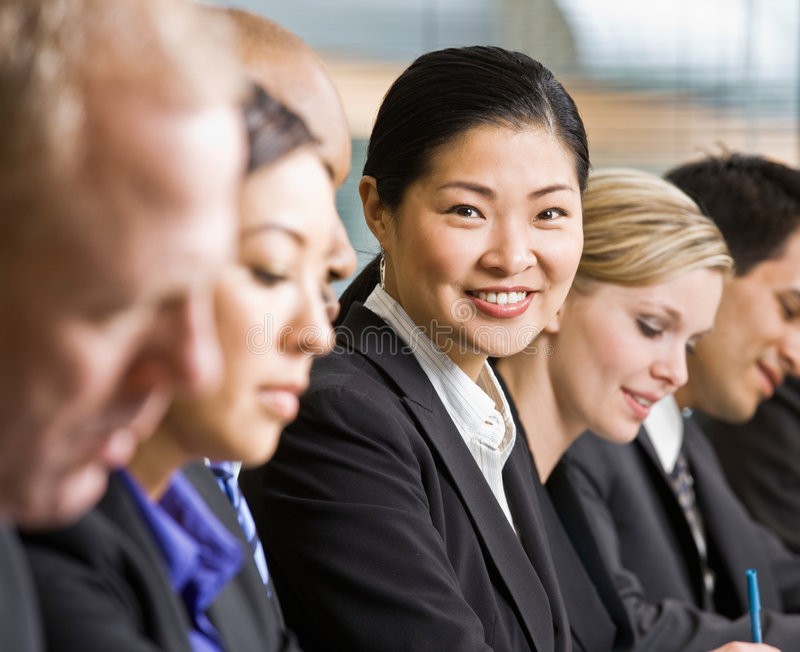 Multi-ethnic co-workers sitting in a row stock photography