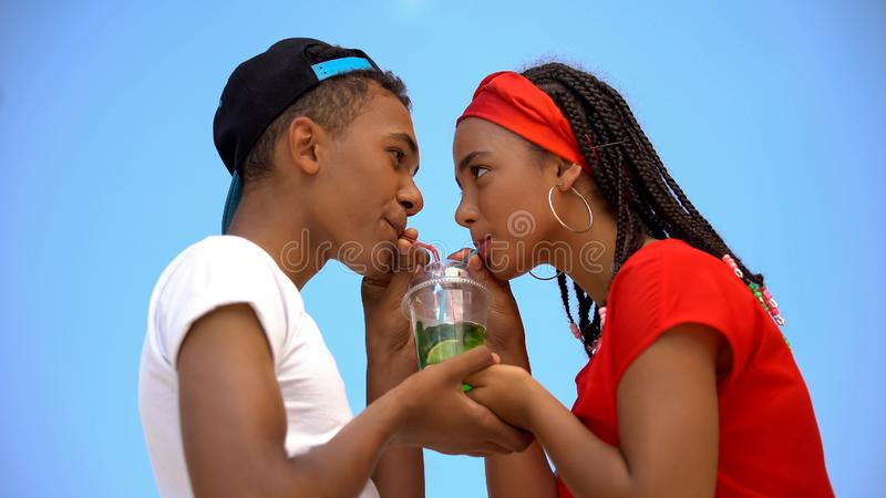 Multi-ethnic couple in love drinking glass of fresh cocktail through two straws royalty free stock photos