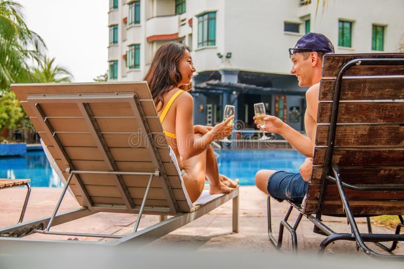 Multi-ethnic couple relaxing next to swimming pool. Happy young couple having cocktails next to swimming pool in hotel stock images