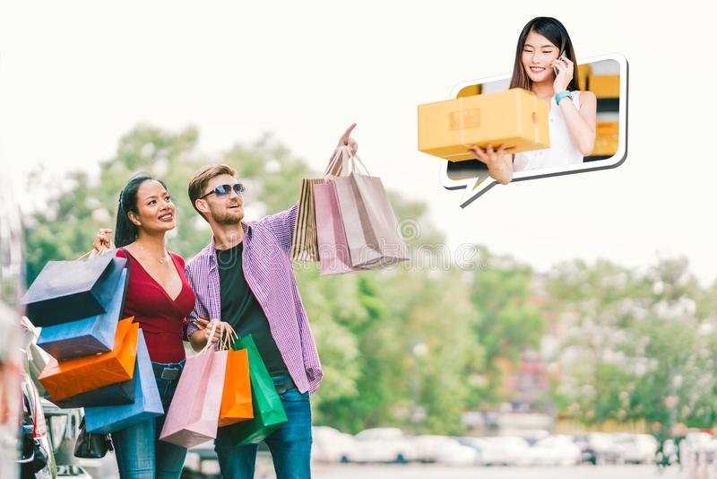 Multi-ethnic couple with shopping bag, man point young small business owner, sell goods on mobile phone call. E commerce concept royalty free stock image
