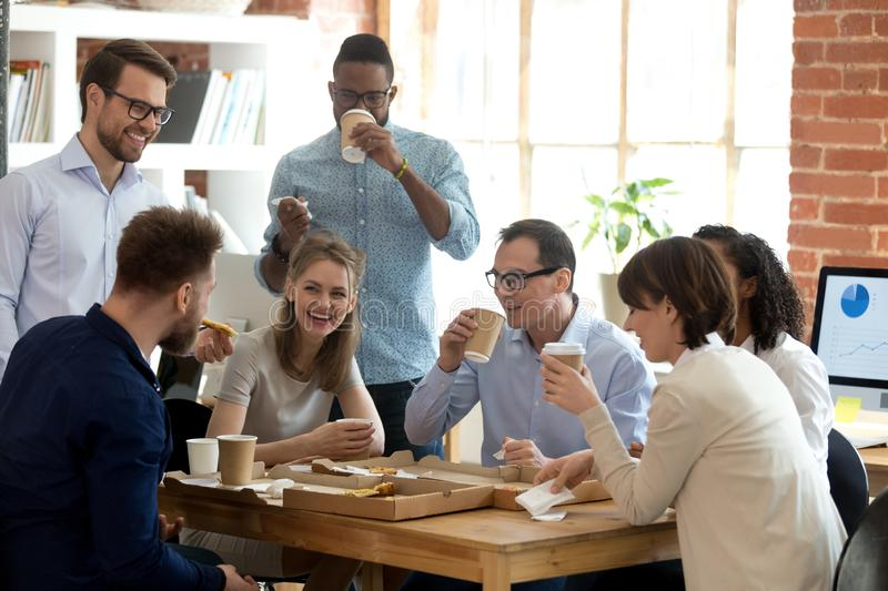 Multi-ethnic employees group enjoy takeaway food friendly conversation in office. Happy diverse team talking having fun drinking coffee eating pizza together stock photos