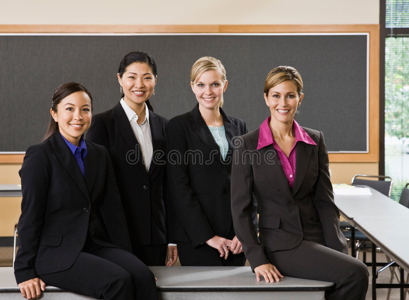 Multi-ethnic female co-workers posing stock photography