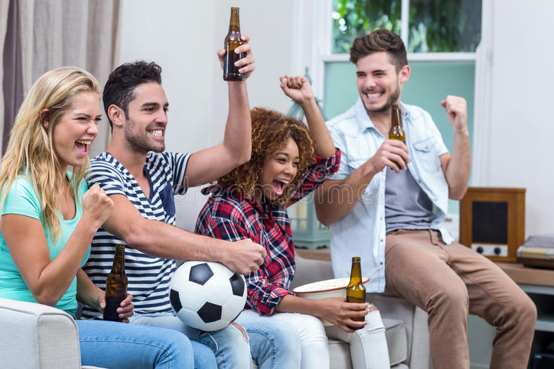 Multi-ethnic friends with beer bottle enjoying soccer match. Happy multi-ethnic friends with beer bottle enjoying soccer match at home stock images