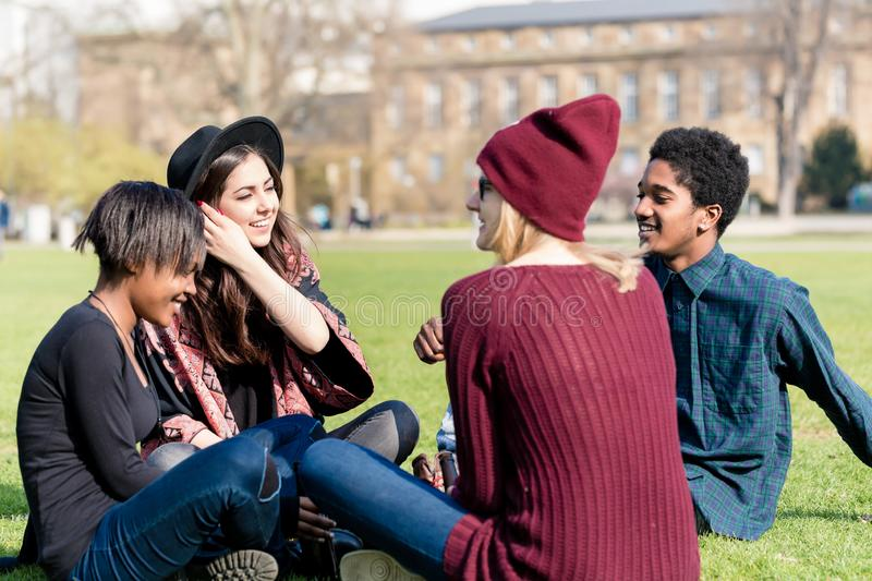 Multi ethnic friends sitting together in the park stock photo