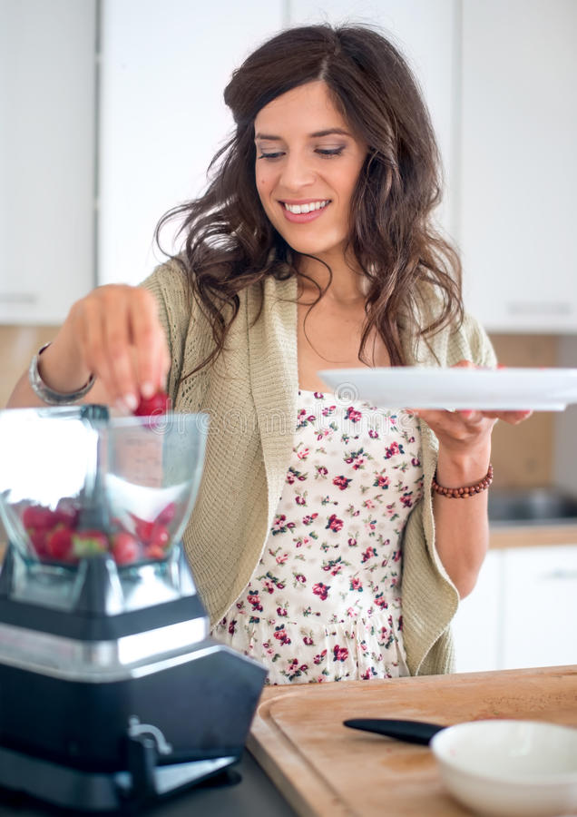 Multi-ethnic girl preparing food in the kitchen royalty free stock images