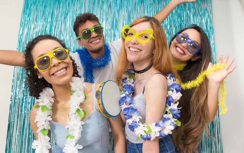 Partygoers are celebrating Carnival in Brazil. Colors: Blue, Green and Yellow. Multi ethnic group of Brazilian friends. Costumed revelers are happy and stock photography