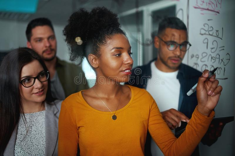 Multi-ethnic group of business people planning startup project on glass board in office royalty free stock photos