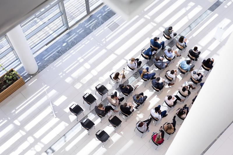 Multi-ethnic group of business people sitting on chair in lobby royalty free stock images