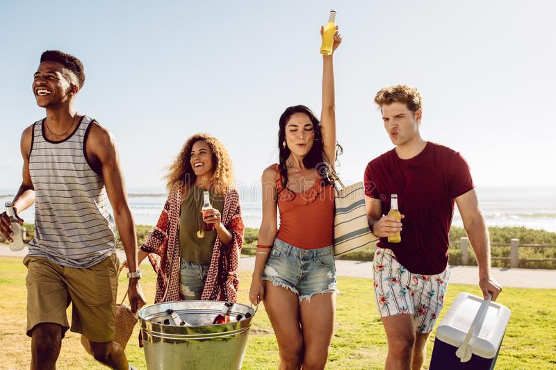 Multi-ethnic group of friends going on picnic. Friends carrying cooler and beverage tub for a picnic on beach. Multi-ethnic group of young people walking royalty free stock photography