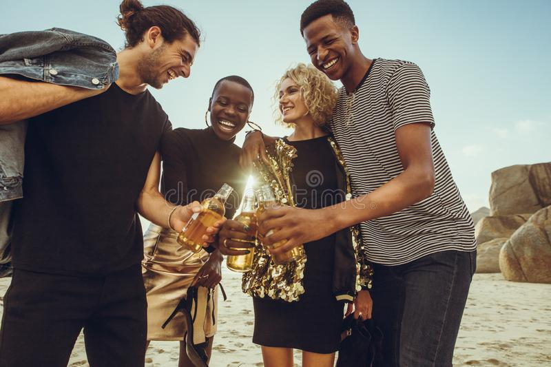 Multi-ethnic group of friends having beers at beach. Multi-ethnic group of friends at the beach having beers. Young men and women at the beach toasting beers royalty free stock image