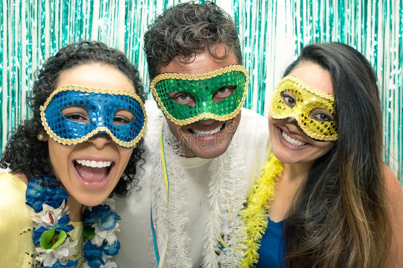Group of Brazilian friends wearing Carnaval costume. Revelers ar. Multi ethnic group of friends is wearing Carnaval masks. Happiness and euphoria. Partygoers are royalty free stock images