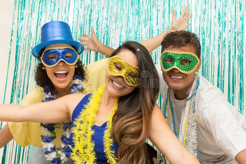 Group of Brazilian friends wearing Carnaval costume. Revelers ar. Multi ethnic group of friends is wearing Carnaval masks. Happiness and euphoria. Revelers open royalty free stock photography