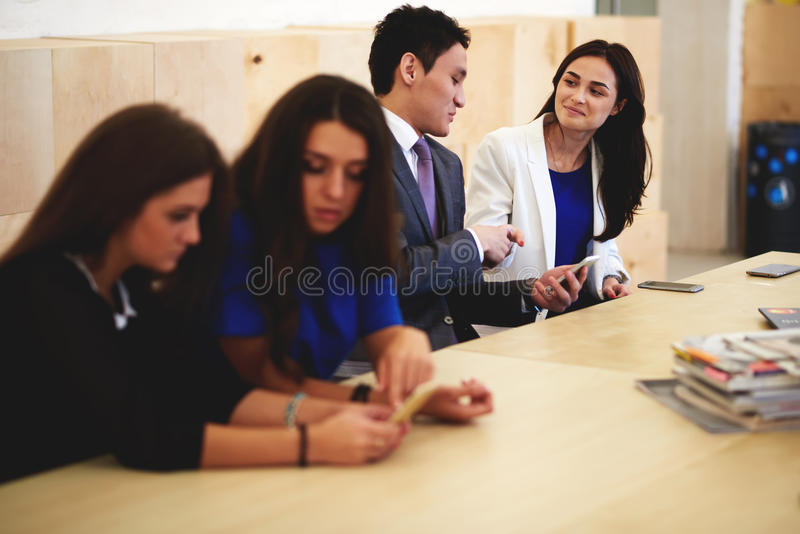 Multi ethnic group of a intelligent financiers using cell telephones during break between meeting wile sitting in conference room,. Young smart people working on royalty free stock image