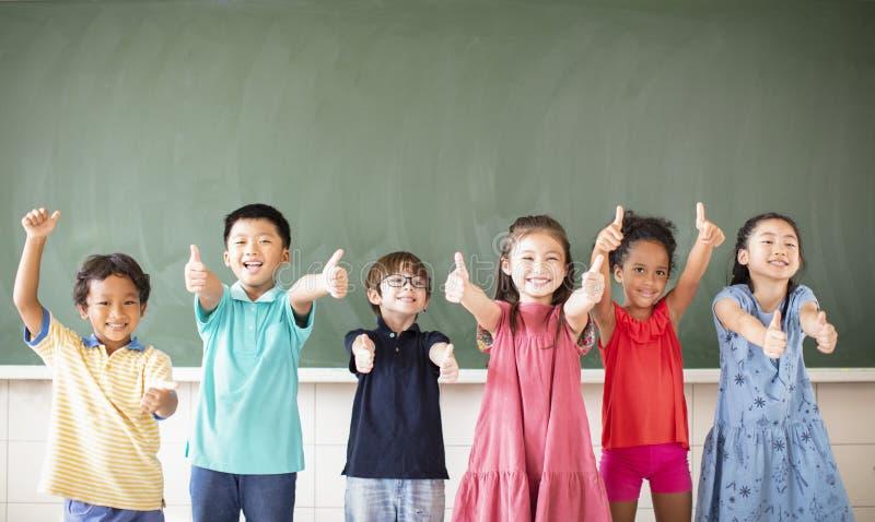 Multiethnic group of school children standing in classroom royalty free stock image
