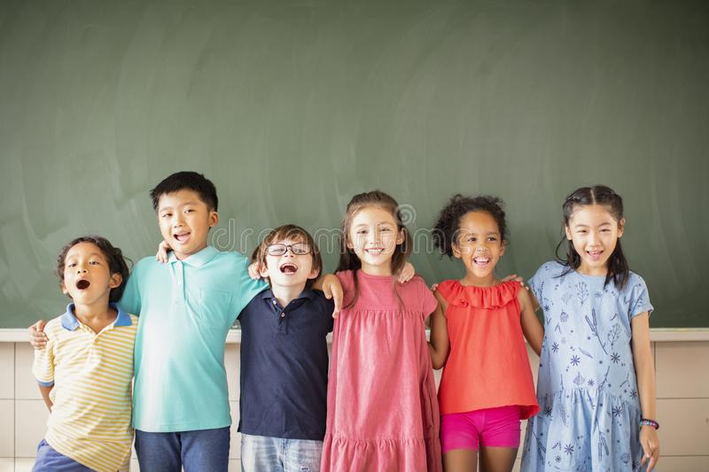 Multiethnic group of school children standing in classroom royalty free stock images