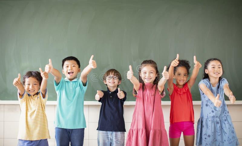Multiethnic group of school children standing in classroom stock photos
