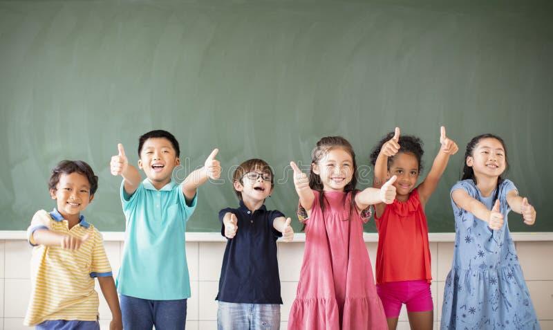 Multiethnic group of school children standing in classroom stock images