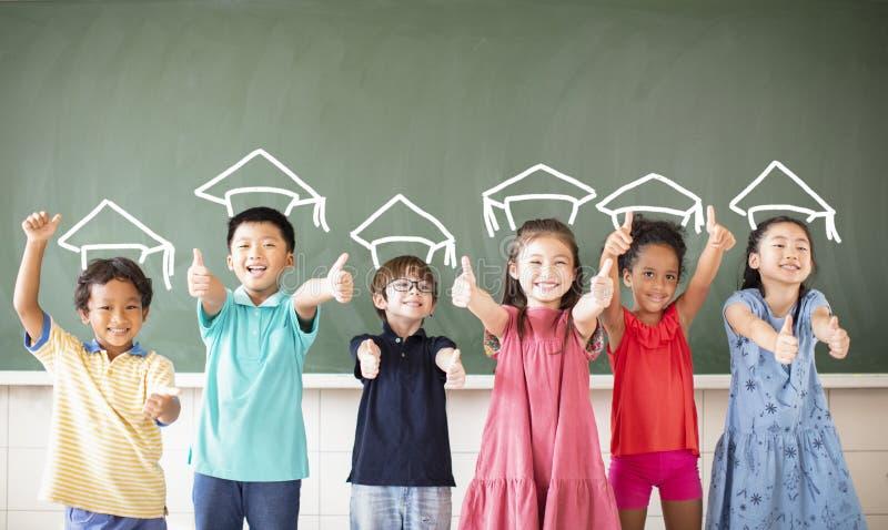 Multiethnic group of school children standing in classroom royalty free stock photos