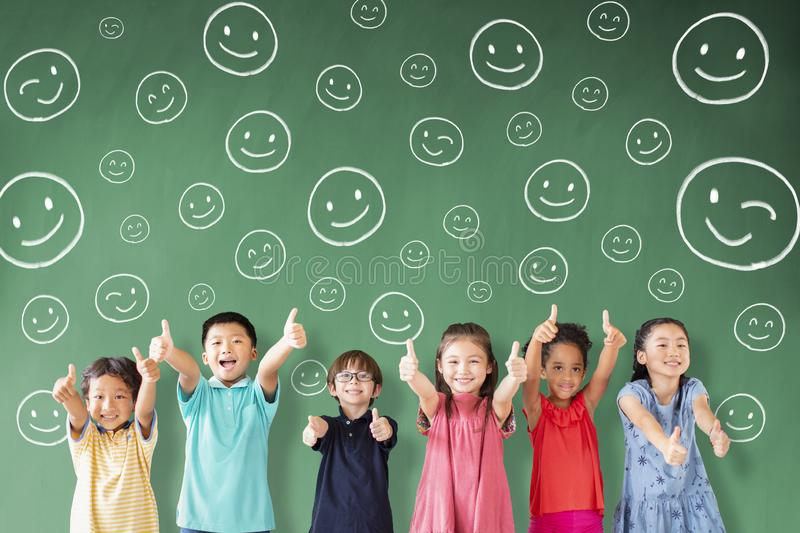 Multi-ethnic group of school children standing in classroom with emotion face. Happy Multi-ethnic group of school children standing in classroom with emotion royalty free stock image