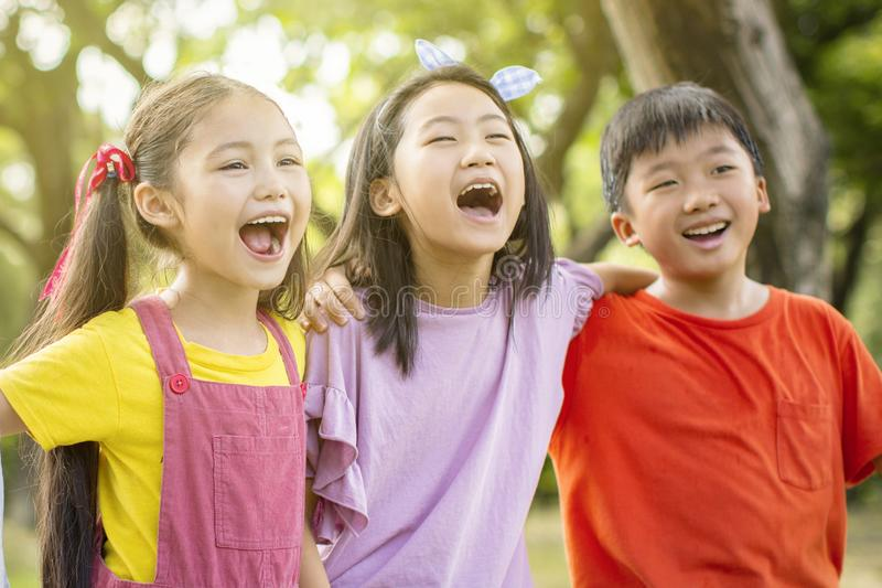 Multiethnic group of school kids laughing and embracing royalty free stock photography