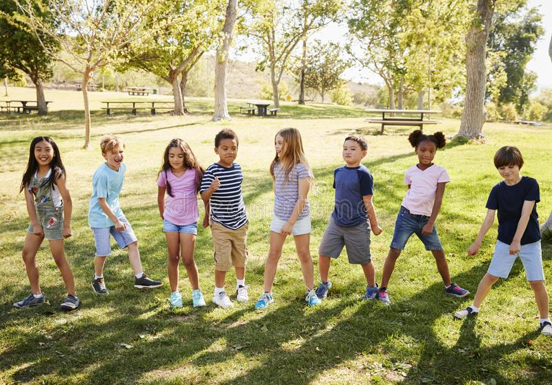 Multi-ethnic group of schoolchildren playing in park stock photos