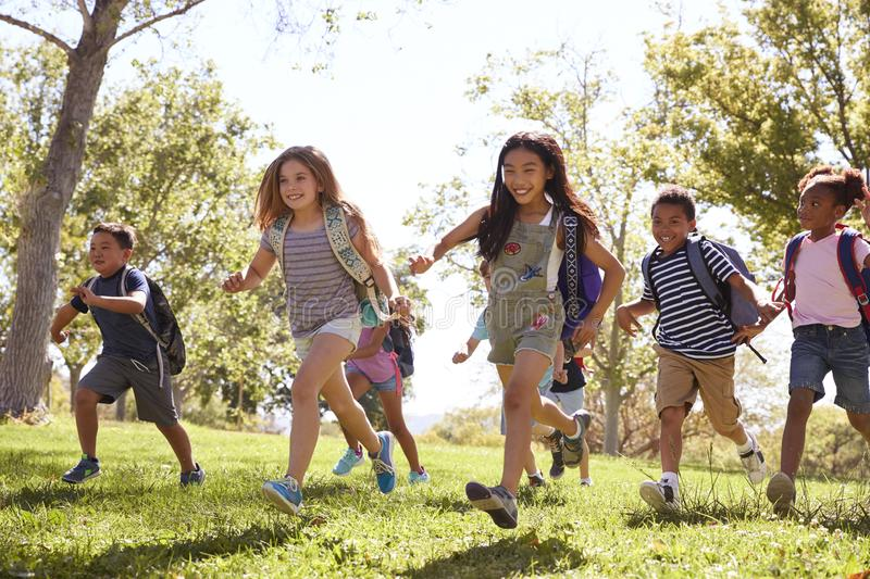 Multi-ethnic group of schoolchildren running in the park royalty free stock photography