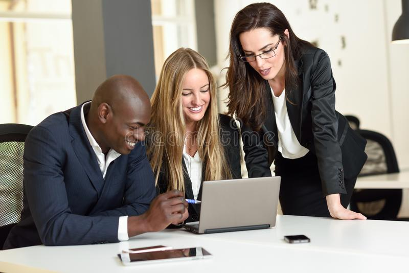 Multi-ethnic group of three businesspeople meeting in a modern o stock images