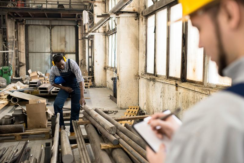 Plant Workers Taking Inventory. Multi-ethnic group of workers wearing overalls taking inventory while standing at spacious production department of modern plant royalty free stock images