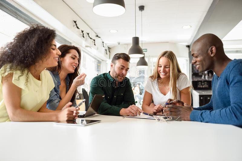 Multi-ethnic group of young people studying together on white desk royalty free stock photos
