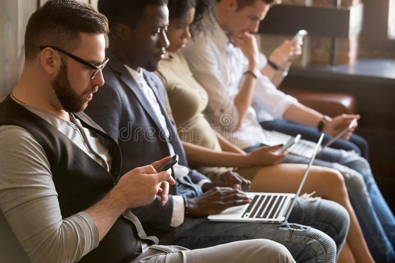 Multi ethnic group of young people using electronic devices indo royalty free stock photos