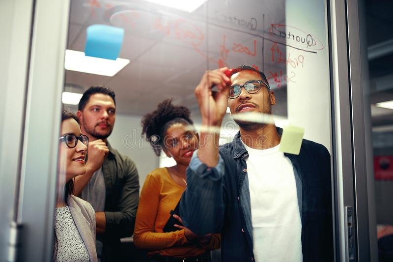 Multi ethnic happy creative business team looking at young man writing ideas on glass board with red marker at office royalty free stock photo