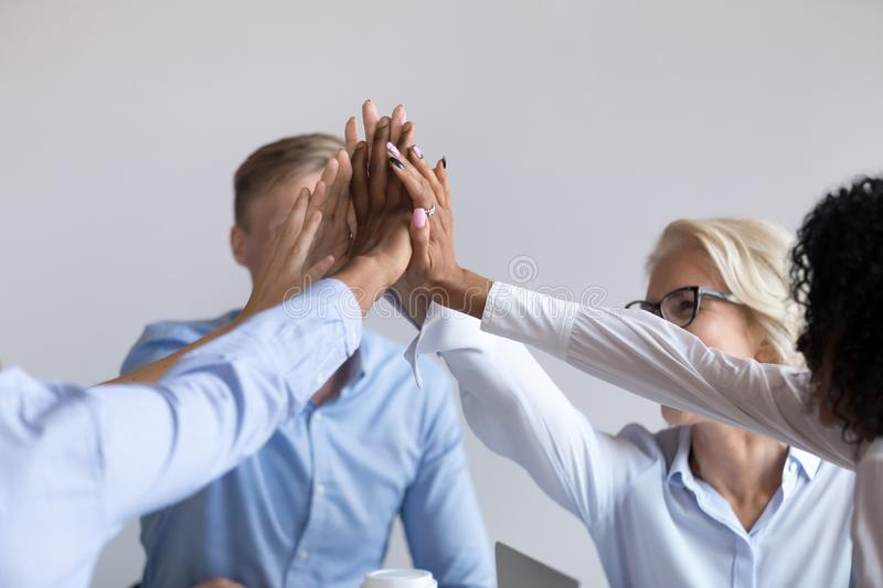 Workmates feels happy giving high five celebrating great work results. Multi-ethnic happy workmates hold touch hands celebrating great work results or successful royalty free stock image