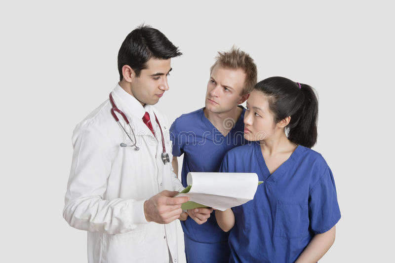 Multi ethnic healthcare professionals discussing medical report over gray background royalty free stock photography