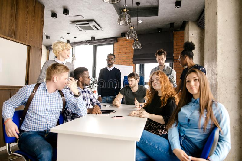 Multi-ethnic meeting of experts of advertisments. Novice lawyers are sharing of experience indoors royalty free stock photos