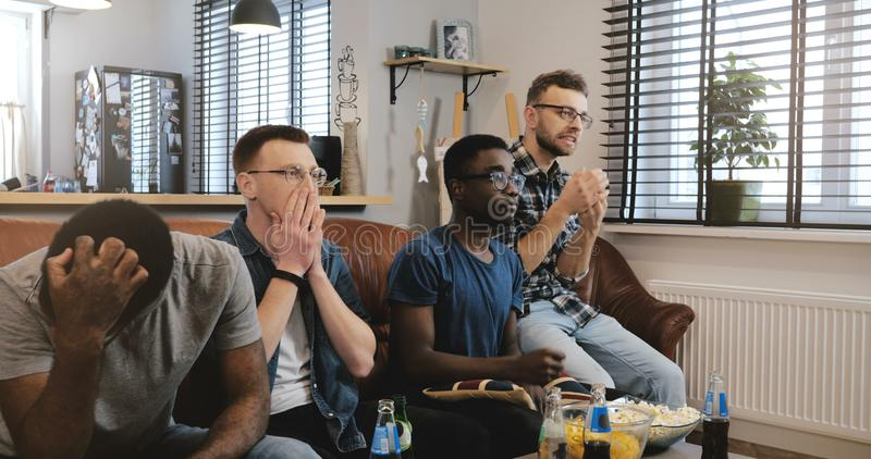 Multi ethnic men disappointed watching sports game. 4K Passionate geeky fans get emotional and sad. Loss and failure. Togetherness. Young casual African stock photography