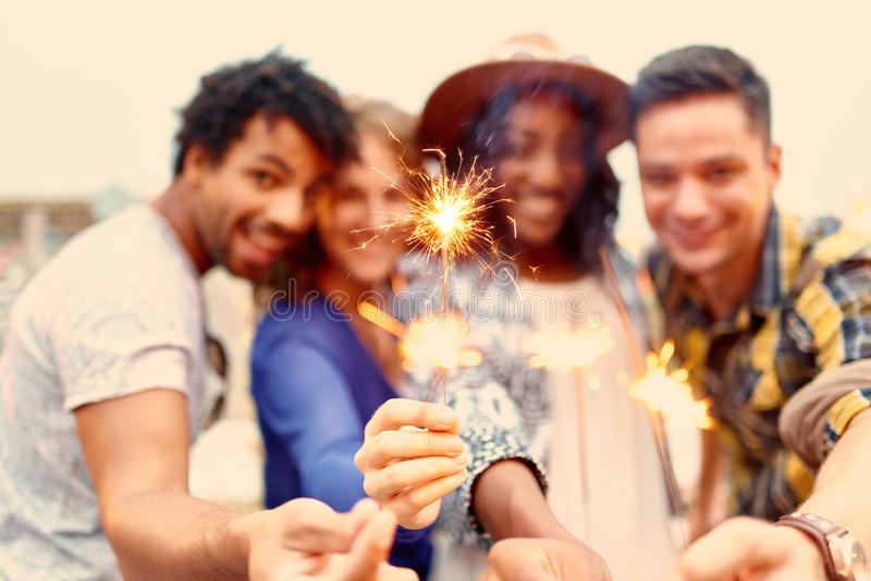 Multi-ethnic millenial group of friendsfolding sparklers on rooftop terrasse at sunset stock photography