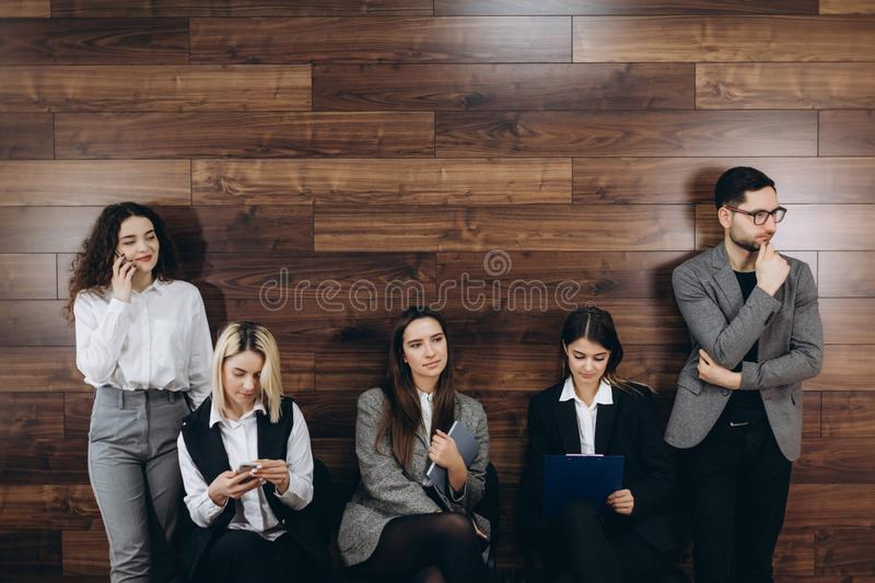 Multi-ethnic millennial people holding phones and resumes preparing for job interview, diverse vacancy applicants candidates wait stock photos